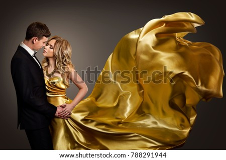 Couple Dancing, Elegant Man and Woman in Fashion Model Gold Dress, Fluttering Gown with Golden Flying Fabric #788291944