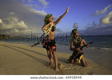 couple dancing hula on the beach at sunrise with the man playing ukulele