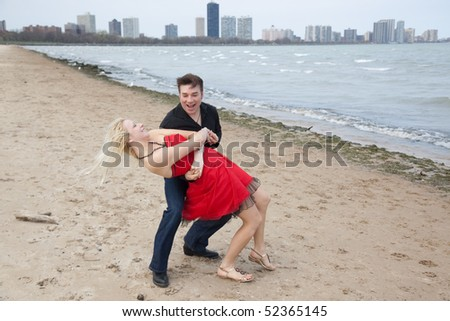 Couple dancing on a beach with a city in the background