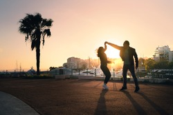 Couple dancing on city street. Spontaneous playful moment with motion. Guy and girl having fun and dating. Stylish trendy people at sunset. Urban life. Silhouette from sun light. Chemistry on a date.