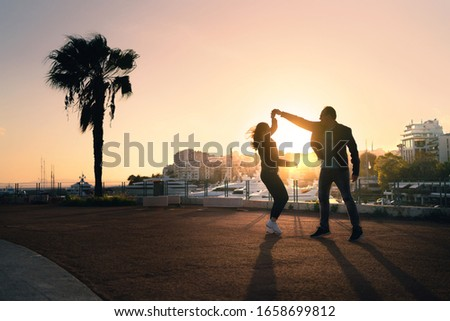 Photo of  Couple dancing on city street. Spontaneous playful moment with motion. Guy and girl having fun and dating. Stylish trendy people at sunset. Urban life. Silhouette from sun light. Chemistry on a date.