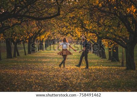 Couple dancing together in autumn nature. Beautiful fun photo #758491462
