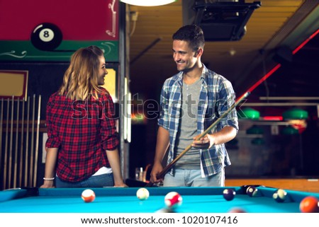 Couple dating, flirting and playing billiard in a pool hall