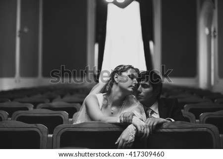Couple daydreams while sitting on the chairs in the theatre #417309460