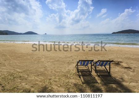 Couple deckchairs on beach at sunset
