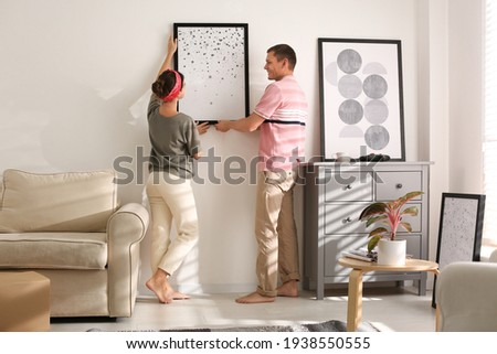Couple decorating room with pictures together. Interior design Stockfoto ©