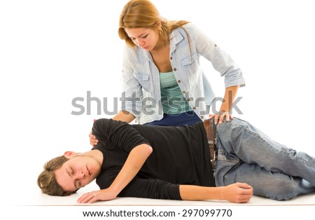 Couple demonstrating first aid techniques with male patient lying in recovery position and female sitting above him. Stock photo ©