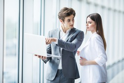 Couple discussing new project on the laptop standing against in office room with panoramic windows