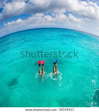 couple dive snorkeling with flippers showing on honeymoon vacation