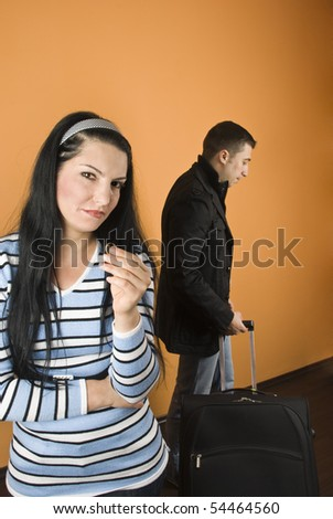 Couple divorce,woman  crying  and stand with arms crossed and holding the wedding ring while the man leaves home