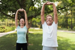 Couple doing exercises in the park. Man and woman doing exercises in the park. They warm up. They do stretching hands