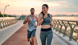 Couple doing sport together on the street. Morning run