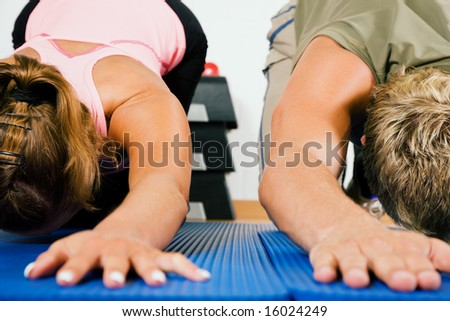 Couple doing stretching and gymnastics on a gym ball