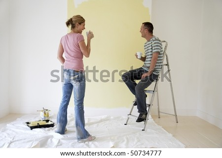 Couple drinking coffee and admiring freshly painted wall