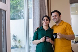 Couple drinking coffee and admiring view from balcony