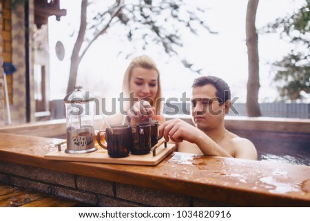 Couple drinking hot tea while sitting in the winter hot spa on the street stock photo