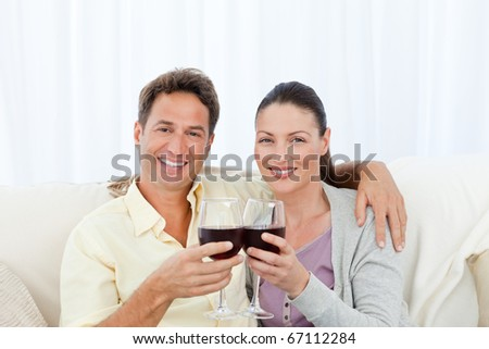 Couple drinking red win on sofa