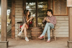Couple drinking tea, coffee in the Wild West, in Western house. Girl in hat with long hair. Girl and boy smile, laughing. Incredible trip, travelers. Sit on the terrace.  Conceptual place
