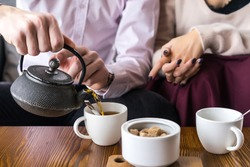 Couple drinking tea in the cafe. White cup of coffee with smoke on table in cafe. Man drinking tea on the wooden table