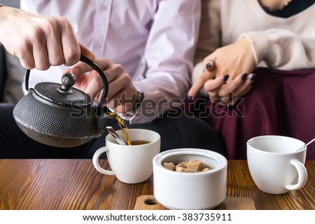 Couple drinking tea in the cafe. White cup of coffee with smoke on table in cafe. Man drinking tea on the wooden table #383735911