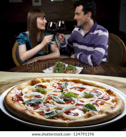Couple drinking wine and eating pizza