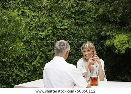 Couple drinking wine, sitting at outdoor table