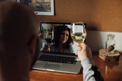 Couple drinking wine while having a video call and chatting remotely during isolation. Social distance, internet dating, relationships concept