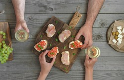 Couple drinking wine with snacks for wine and grapes on a wooden table, top view