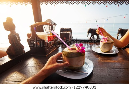 Couple drinks sweet fresh coconuts decorated with flower at restaurant on the beach at sunrise #1229740801