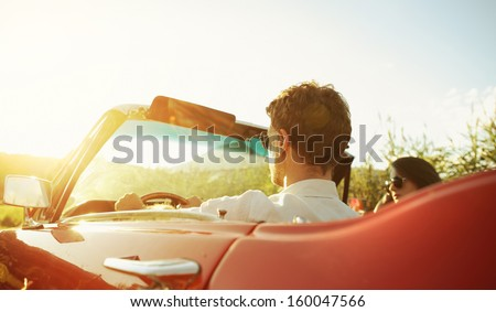 couple driving convertible car...