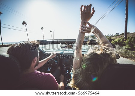 Couple driving on a convertible car - Shutterstock ID 566975464