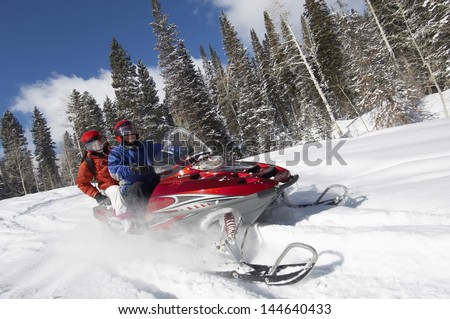 Couple driving snowmobile on snow covered track Stock photo ©