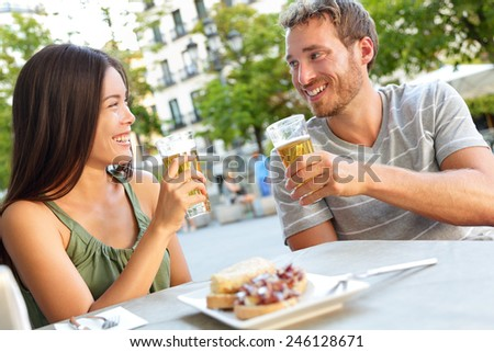 Couple eating tapas drinking beer in Madrid, Spain. Romantic man and woman enjoying local traditional food on square in Madrid. Asian woman and Caucasian man dating. #246128671