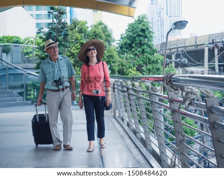 couple elderly travel in city,old man and elder woman walking around city
