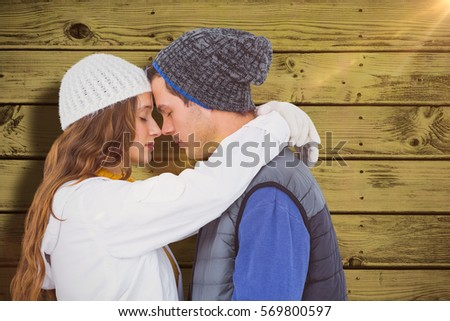 Couple embracing head to head against blue paint splashed surface #569800597