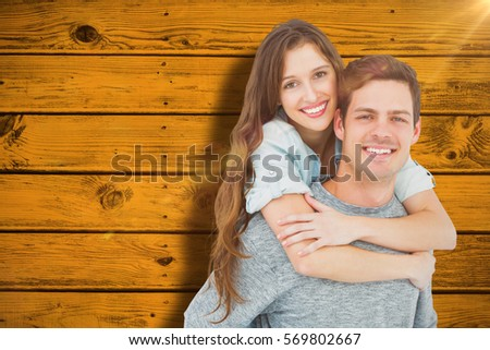 Couple embracing with arms around against yellow paint splashed surface #569802667
