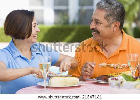 Couple Enjoying A Barbequed Meal In The Garden - stock photo
