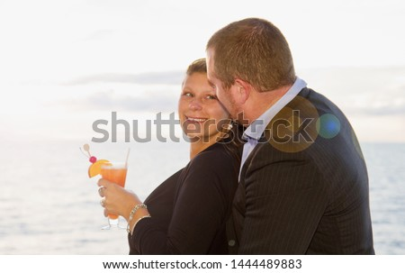 Couple Enjoying a Cruise Vacation, relax and cuddle on the ship's deck while drinking a cocktail