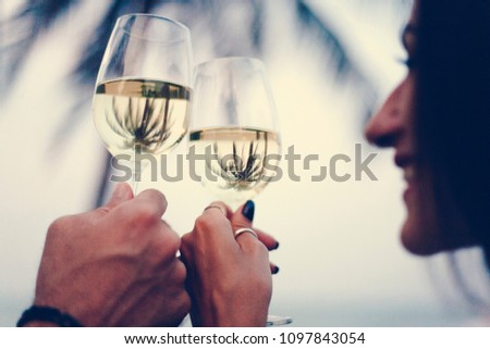 Couple enjoying a glass of wine by the beach #1097843054