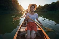 Couple enjoying a ride on a canoe. Smiling couple paddling boat on the sunset lake