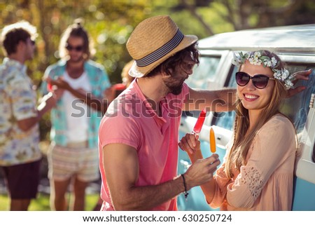 Couple enjoying and eating ice lolly in park
