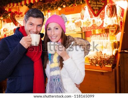 couple enjoying hot wine punch claret on christmas market