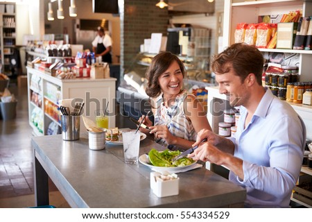 Couple Enjoying Lunch Date In Delicatessen Restaurant