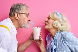 couple enjoying milk cocktail drinking from one glass with two straws, aged man and woman on date. 14 february, st valentines day concept, love. isolated on pink background