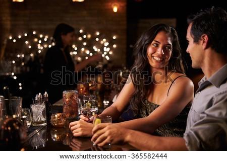 Couple Enjoying Night Out At Cocktail Bar #365582444