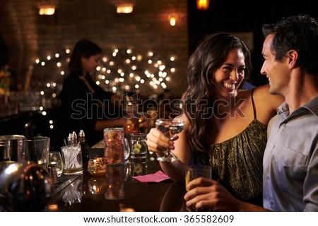 Couple Enjoying Night Out At Cocktail Bar #365582609