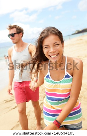 Couple enjoying romantic beach vacation holiday, Young modern trendy cool multi-ethnic couple having fun laughing together smiling happy. mixed race Asian woman, Caucasian man.