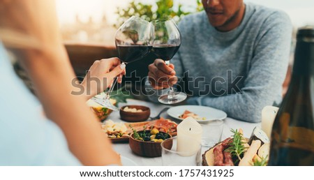 Couple enjoying romantic dinner at restaurant terrace drinking red wine and eating healthy mediterranean food, Lovely couple making cheers with red wine glasses at summer day at terrace