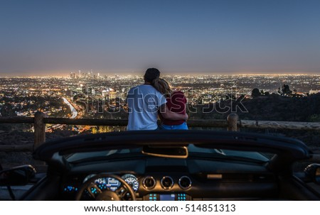 Couple enjoying skyline view from their car in the night. Focus on the Los angeles city in the background