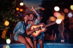 Couple enjoying summertime next to swimming pool,enjoying in music.